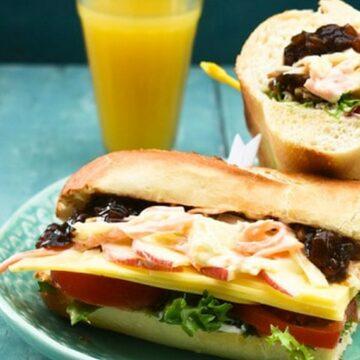 A cheese ploughmans sandwich on baguettte,