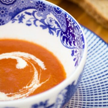 A bowl of vegan tomato soup with a swirl of cream