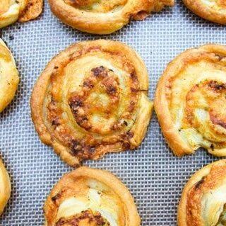 Vegan pesto cheese swirls on a baking sheet
