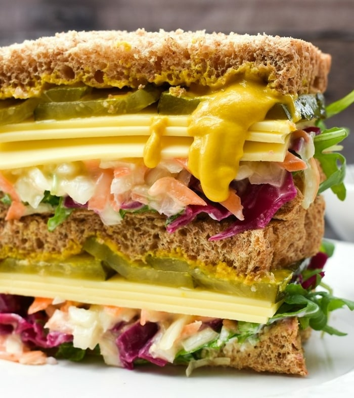 A close up of a vegan New York deli sandiwhich with mustard oozing out
