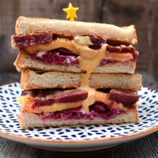Vegan Reuben Sandwich stacked on a patterned plate