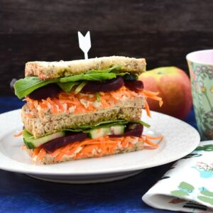 Hummus, beetroot and salad sandwich served with a red apple