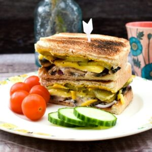 Grilled Cuban Sandwich served with tomatoes and cucumber