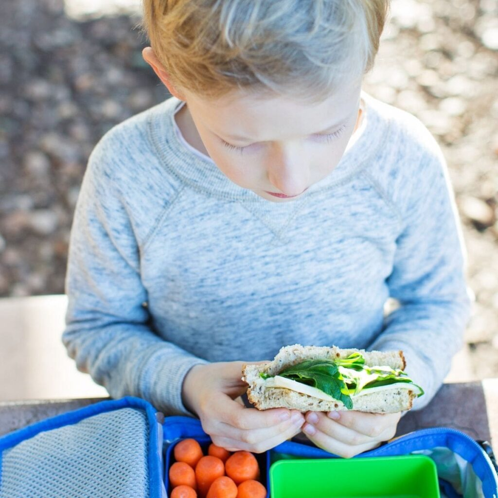 child eating a packed lunch