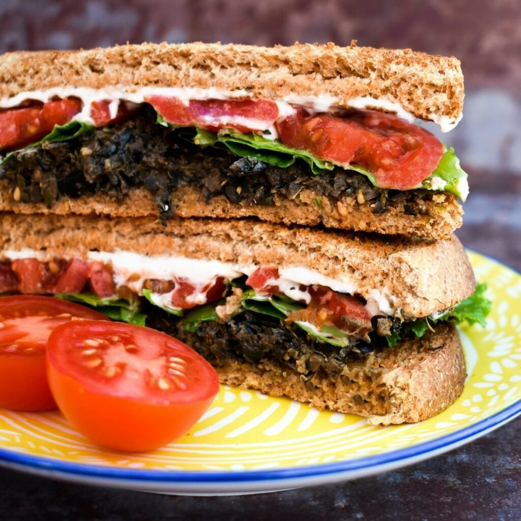Vegan Olive & Tomato Toastie stacked on a yellow plate